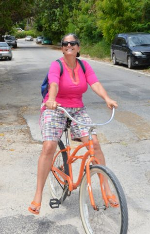 A smiling woman in pink shirt leans back on an orange cruiser bicycle