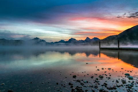Steam rises from a placid lake with mountains jutting into cloudy sky lit by a sunset or sunrise