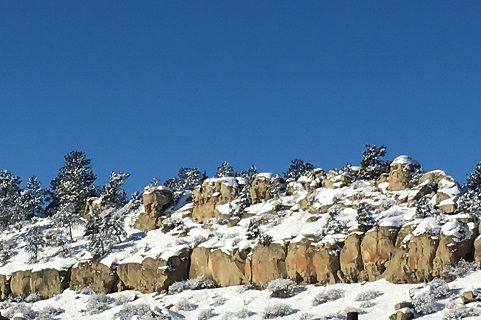 Snow dusts shrubs and trees on a rocky rim below blue sky