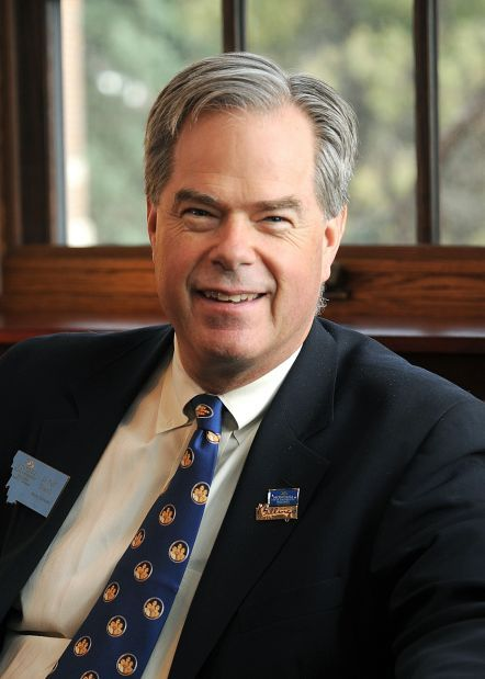 A smiling man with gray hair in a white-button up shirt, blue tie with gold, circular accents, and black jacket with pin and Montana emblems on his lapels