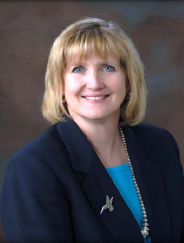 A smiling blonde woman leans forward in navy blue blazer with bird pin on her lapel