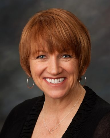 A smiling woman with short red hair