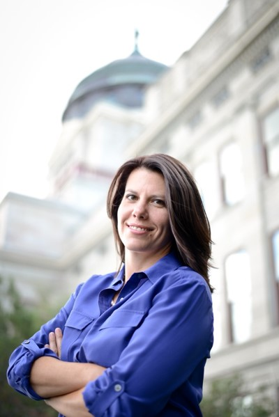 A smiling woman in a blue button-up shirt with crossed arms leans back in front of a capitol building