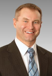 A smiling man with blue eyes, blue tie, white shirt, and gray suit jacket