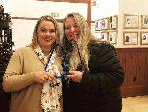 Two smiling women hold clear awards