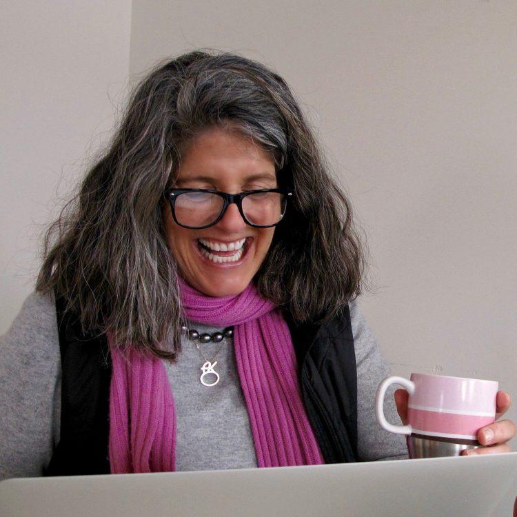 Amy Kellogg laughs while holding a pink mug