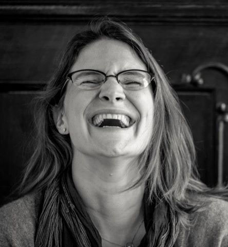 A woman leans her head back and laughs